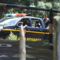 Dentro de la garita se logra ver una patrulla de la PNC de Alta Verapaz. En su interior un policia porta un arma utilizada para lanzar gases lacrimogenos. Foto: Gustavo Illescas.