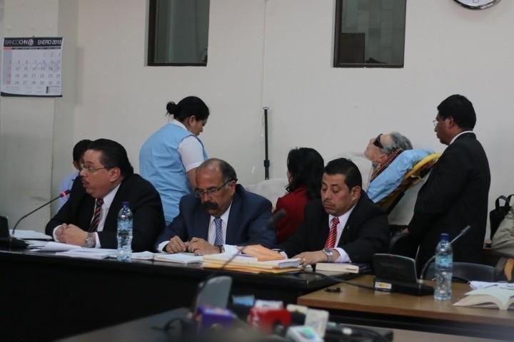 Los abogados de Efraín Ríos Montt, mientras el ex dictador descansa atrás. Foto: Roderico Yool.