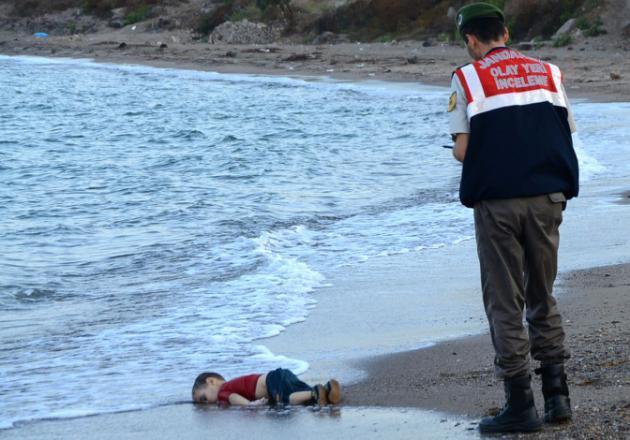 """"""" Un oficial de la Policía turca observa el cuerpo de un niño inmigrante ahogado en las costas de Bodrum, sur de Turquía, el 2 de septiembre de 2015 AFP/Dogan News Agency/AFP - Un oficial de la Policía turca observa el cuerpo de un niño inmigrante ahogado en las costas de Bodrum, sur de Turquía, el 2 de septiembre de 2015"""" Foto: AFP tomada de yahoo noticias"""